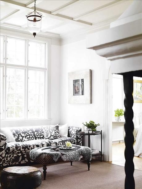 The graphic black and white pattern on the sofa really pops against the white walls and ceiling of this room.