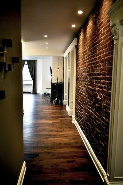 exposed brick, hardwood floors, white baseboard trim