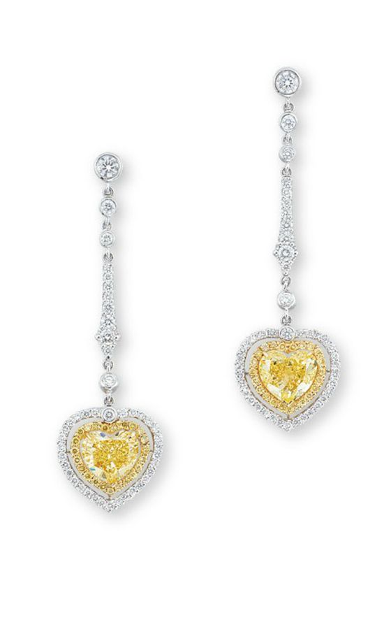 A PAIR OF COLOURED DIAMOND AND DIAMOND EAR PENDANTS  Each set with a heart-shaped fancy intense yellow diamond weighing approximately 1.41 and 1.30 carats, within a two-tiered brilliant-cut yellow diamond and diamond surround, suspended from a line of collet-set brilliant-cut diamonds and link, mounted in platinum and 18k gold, 4.4 cm long