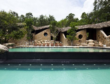 Nine stone cabins are sheltered beneath a single thatched roof in this addition to a hotel resort in Nha Trang, Vietnam