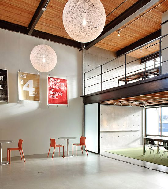 Turnstyle office Graham Baba Architects Ballard Seattle. Uniqiuw light fixtures and color accents and wall art break up the simple rustic area. #interiordesign #decor #office