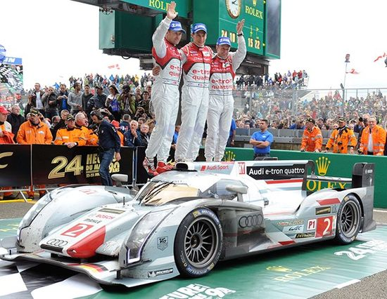Audi Sport's Tom Kritensen, Loic Duval and Allan McNish celebrate at Victory Circle at #LeMans. The car completed 348 laps around La Sarthe, just over 2946 miles.