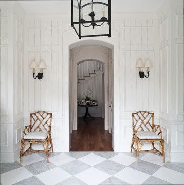 Grey and white marble, white molding on top of paneling, an oversized lantern fixture, and a pair of cane side chairs. Perfect.