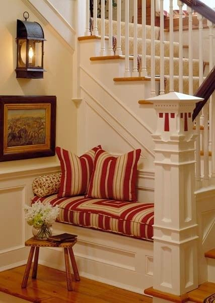 bench in nook of staircase - could even make into a pull-out bed for when you have guests visiting.  Great use of space!