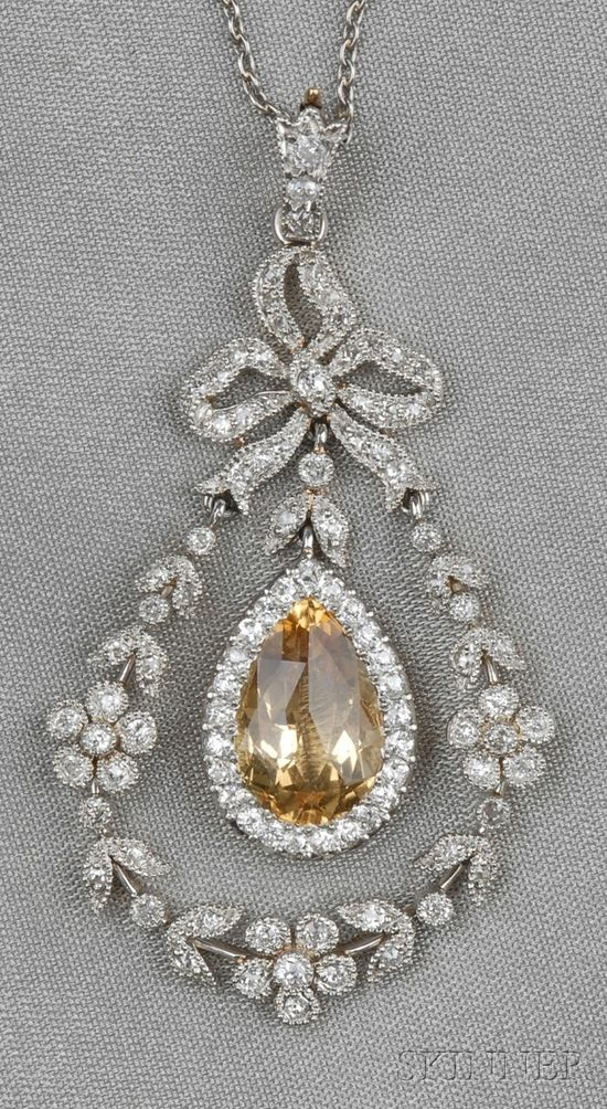 Edwardian Topaz and Diamond Pendant, Black, Starr & Frost, set with a faceted topaz measuring approx. 12.00 x 7.00 x 5.40 mm, framed by an old mine-cut diamond melee garland, surmounted by a bow, lg. 1 3/4 in., signed B.S, and suspended from platinum chain.