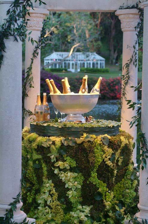 Chilled bottles of champagne await guests on a table covered with leaves, moss and green-hued flowers.