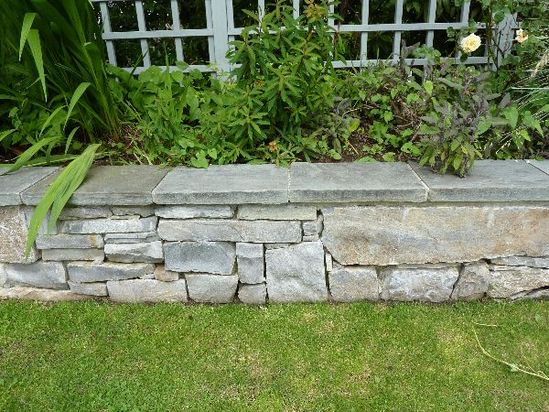 A great looking stone flower bed made with panels