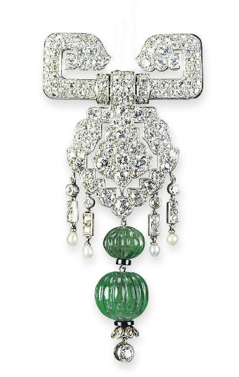 AN EXQUISITE ART DECO EMERALD AND DIAMOND BROOCH, BY #CARTIER   The two fluted emerald beads with a diamond collet detail at terminal, suspending from a pavé-set diamond openwork shield-shaped panel set with a seed pearl and diamond fringe, to the diamond buckle surmount, circa 1930, 6.7 cm long, in original Cartier red leather case  Signed Cartier London