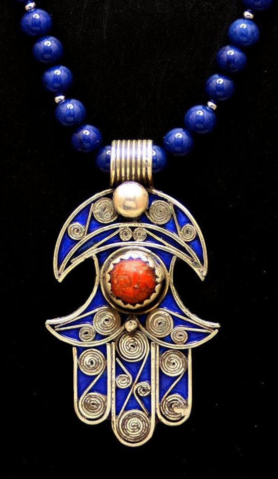 """Hamsa - the Hand of God - is worn in many cultures to protect against evil spirits, demons, the evil eye. - This Hamsa was handmade in Morocco and features Life Spirals on front and reverse side. The cobalt blue enamel is in excellent condition. The center Coral is an old cabochon and is set in an unusual scalloped bezel. The Life Spiral is believed to represent the travel from the inner life to the outer soul or higher spirit forms; the concept of growth, expansion, and cosmic energy. 2 3/8"""" L"""