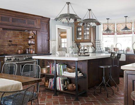 dark wood, color of blue on the walls, fabric on windows, metal bracing for bookshelves on island, warm colored tile on floor and stove backsplash