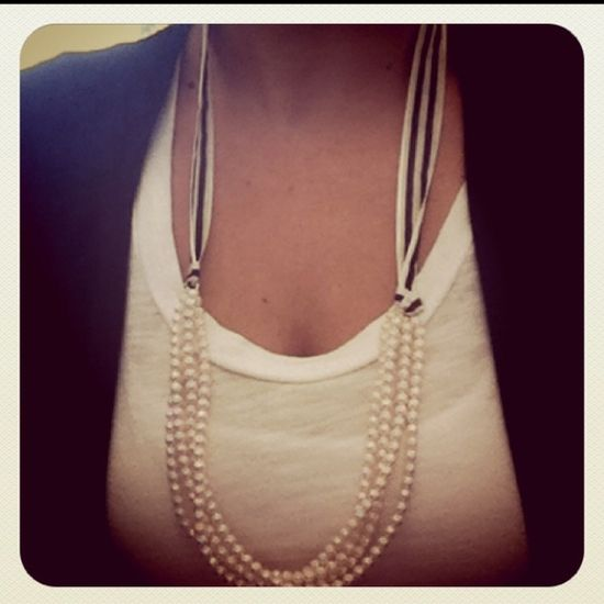 Attach a ribbon to a pearl neckace or any necklace.