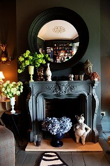 Likes: Circular mirror, matching wall and fireplace, tiered floral arrangements
