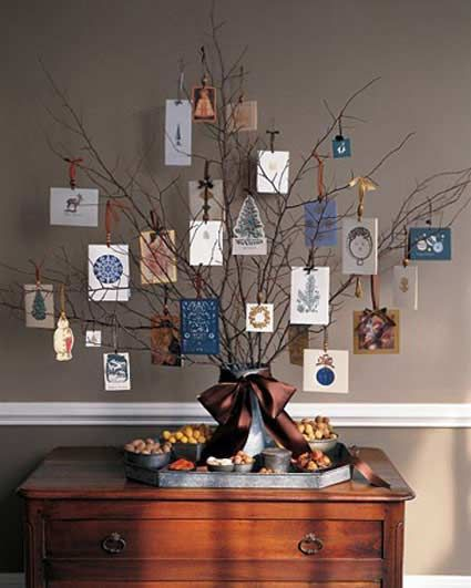 """Make yourself a Christmas tree out of gathered twigs and branches. Place the branches in a vase and tie a beautiful satin bow around it. Old Christmas cards make interesting and cheap Christmas decorations for your new """"tree."""""""