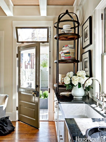 This Savannah Kitchen is an interesting mix of elements, from the over sized chandelier, to the etagere shelves on the counter, to the slat ceiling, and the grass under the farm table - yes, this kitchen has character.  Now, where would I find a fork?
