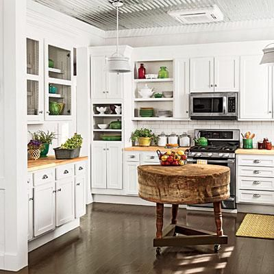 An antique butcher-block provides additional workspace in the kitchen, which is not large enough for a traditional island. A simple tripod with casters elevates it to standard counter height and enables it to be moved around easily.