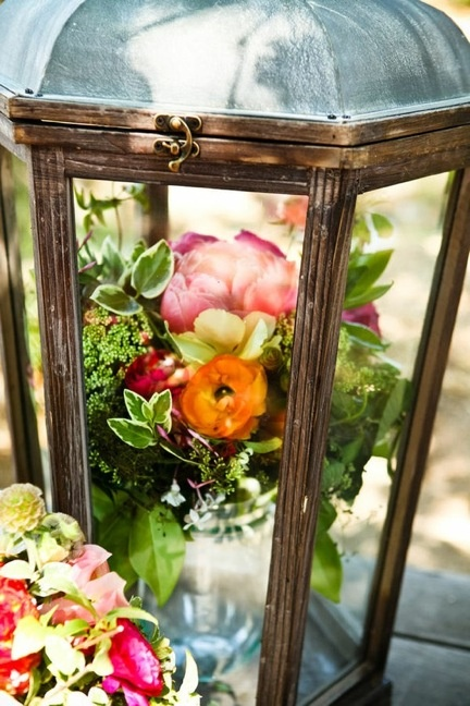 Flowers in a vase inside a lantern. Gorgeous centerpiece