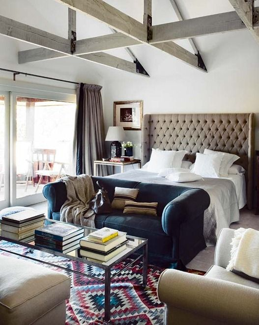 An eclectic bedroom. Love the beige, white and jewel toned color scheme, rustic wood beams, glass coffee table, tufted headboard, navy sofa and the tribal rug.