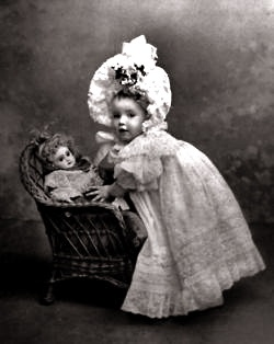 antique portrait of a baby girl posing with her Bébé Jumeau doll, c. 1890-1900