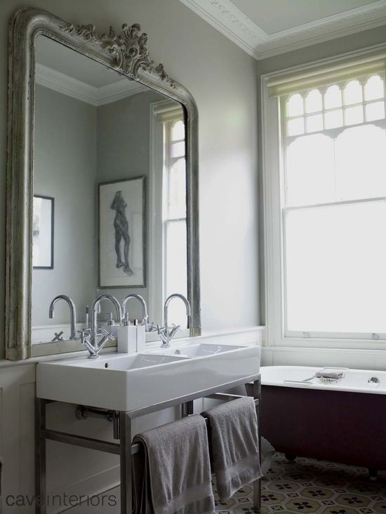 Love the large vintage mirror over the modern fixtures (Cave Interiors)