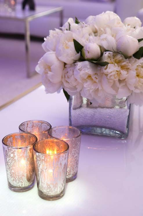 The warm glow of candles in mercury glass set a romantic tone among blooming peonies in a square vase.