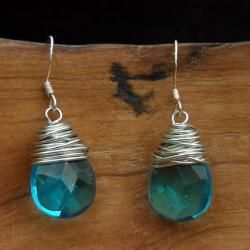 Add a touch of color to your outfit with handmade jewelry from China. These earrings feature facetted blue glass raindrops wrapped with silver wire.