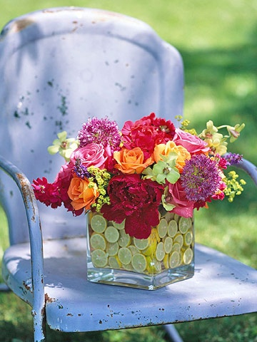 Double Vase with a Twist-For a modern look, layer two square glass vases -- one 6 inches, one 4 inches -- and float slices of key limes in water between the two. Roses, peonies, allium, salvias, and geraniums burst from the top of the vases.