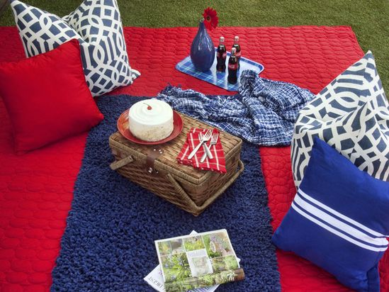 Delineate a portion of your picnic area as a serving space by layering a contrasting bath mat or small area rug in the center. Utilize the surrounding space for lounging.