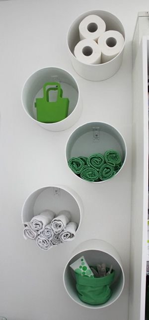 Cylindrical cardboard tubes (used for concrete formwork and available @ home depot)...painted and used as wall hung storage containers