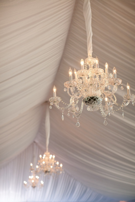 a beautifully draped tent with gorgeous chandeliers