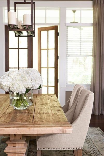 Beautifully designed dining room! Notice the unique candle chandelier and rustic wooden table. Thanks to Southern Charm for the photo.