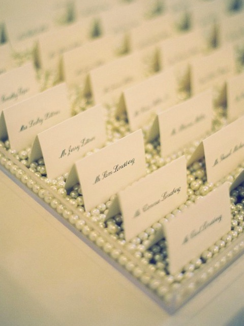 Place cards on a bed of pearls.