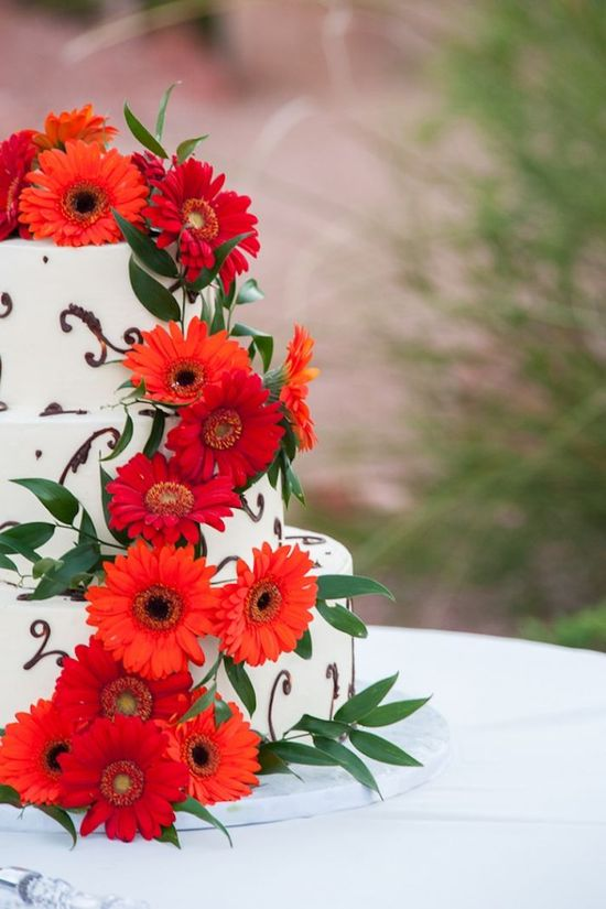 Bright orange and red blooms on white wedding cake