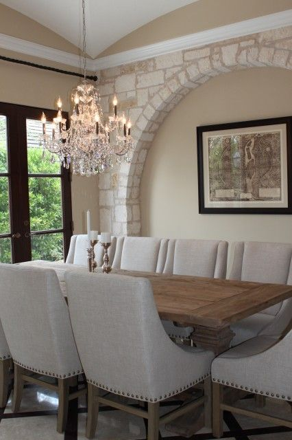 An elegant, neutral toned dining room features a stone arch, crystal chandelier, and a trestle table of reclaimed wood  (via CG DESIGN INC.)