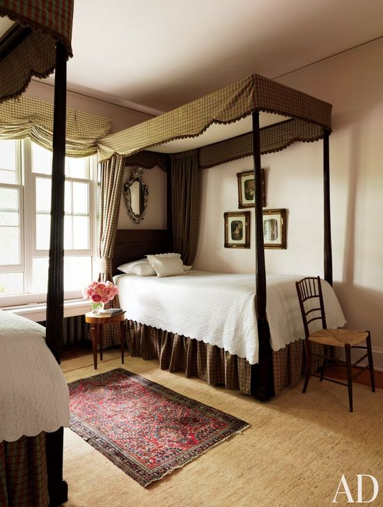 A bedroom in a Dutchess County, New York, home features quilted coverlets by Schweitzer Linen. On the wall are 1850s portraits of the owner's ancestors.