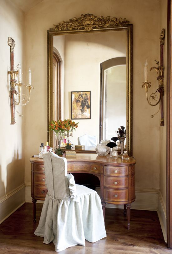 Place mirrors where you want a window, in this picture a very tall mirror is placed above a table of the same width, serves as a window sill like look and enlarges a very small area of a room.