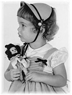 Little girl with her doll circa 1950. Love her dress and hat!