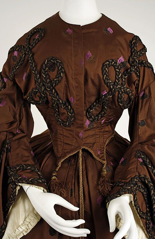 1858-1860 Brown silk with pink leaf design dress.  Has double points on bodice front, heavy brown braid trim, American, bodice closeup.