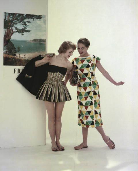 Two models wearing beachwear, with one wearing a black striped beach suit and the other wearing a harlequin patterned dress, 1955. #vintage #fashion #summer #1950s