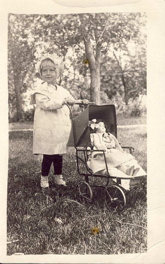 Little girl with beautiful doll in doll carriage. Great photo, circa 1910.