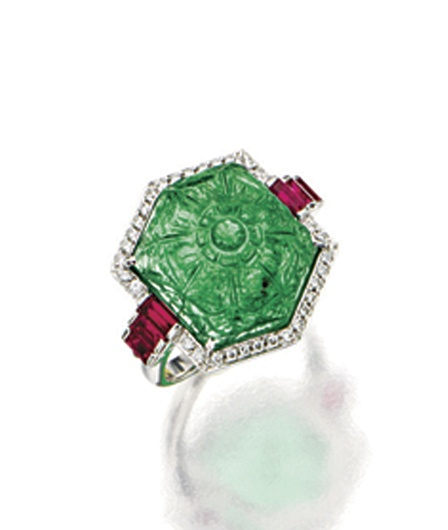 EMERALD, RUBY AND DIAMOND RING.  Centring on a hexagonal carved emerald weighing approximately 7.50 carats, within a surround of brilliant-cut diamonds, flanked by rectangular step-cut rubies together weighing approximately 1.20 carats, mounted in platinum.