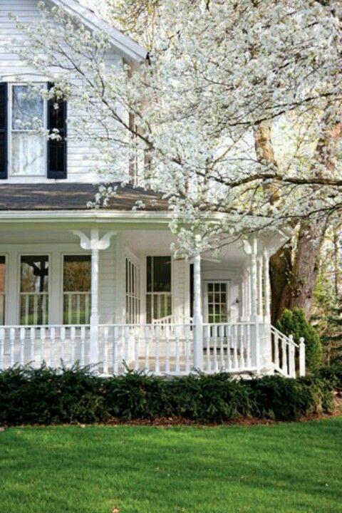 An old farmhouse with a wrap around porch-