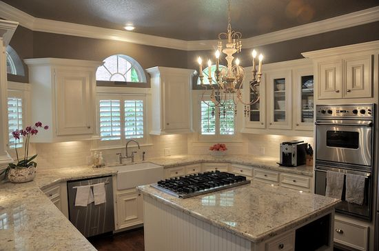 Cote de Texas - kitchens - Benjamin Moore - Stardust -  farmhouse sink, bridge faucet, arched kitchen window, plantation shutters, white kitchen, glass fronted cabinets,  wall mounted oven, stainless steel double oven, granite countertops, crown molding, bianco romano granite