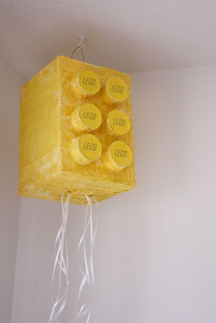 I wonder if I could collect enough peanut butter jar lids by the party for the front.  Lego Pull Pinata. #legoduploparty