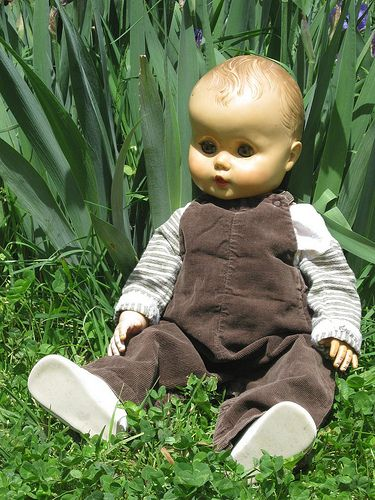 very old doll wearing vintage baby clothes