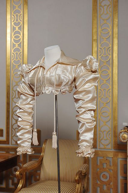 Cream silk satin spencer, c. 1818. Worn over high-waisted gowns. Highly decorated in imitation of military uniforms. Courtesy of Worthing Museum.