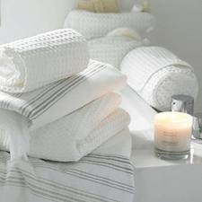 white towels and candles in a white bathroom