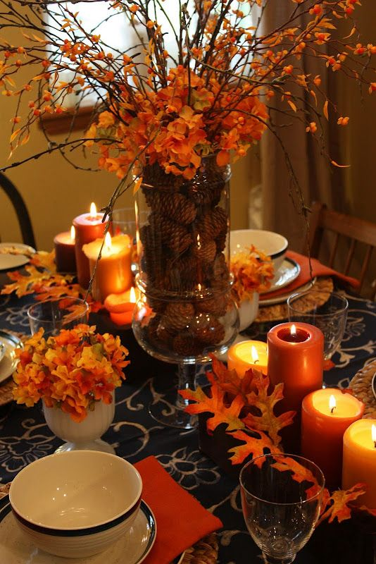 Fall tablescape - I love candles.  the large oak leaves are stunning and walnuts in a glass vase is perfect to stabilize those tall wispy fall branches  (they use pine cones here which looks nice but can be too light weight depending on the weight of the floral arrangement.