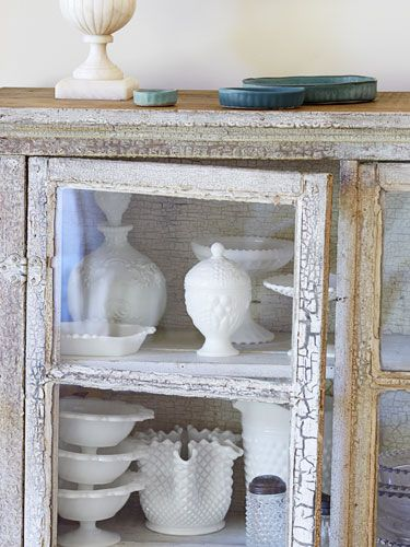 Create a rustic display: An antique cabinet, in its original paint, contains milk glass. #storage