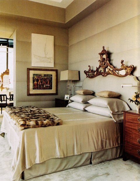 Deco style upholstered wall, antique carved headboard, gold washed neutral colors and a little fur = stylish glam bedroom