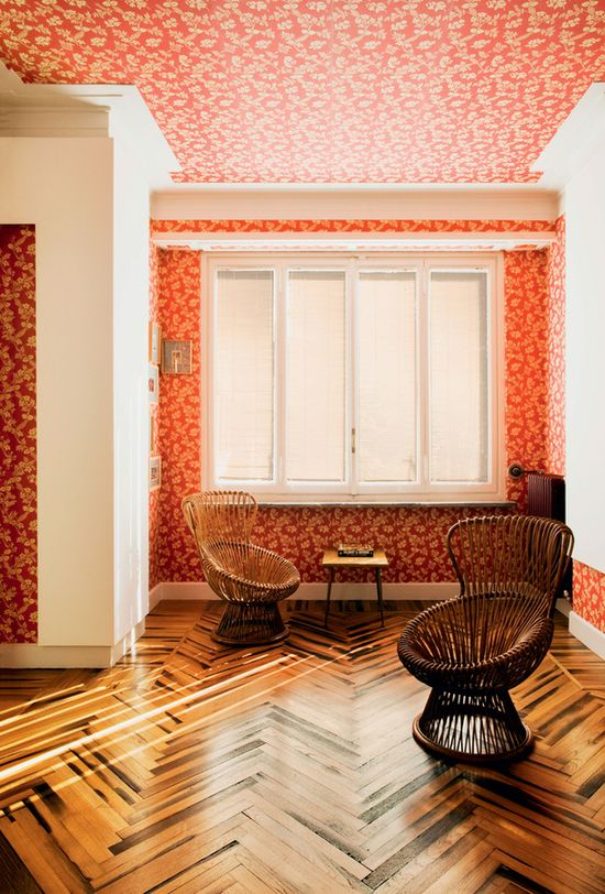 Patterned wallpaper, parquet flooring and wicker chairs.
